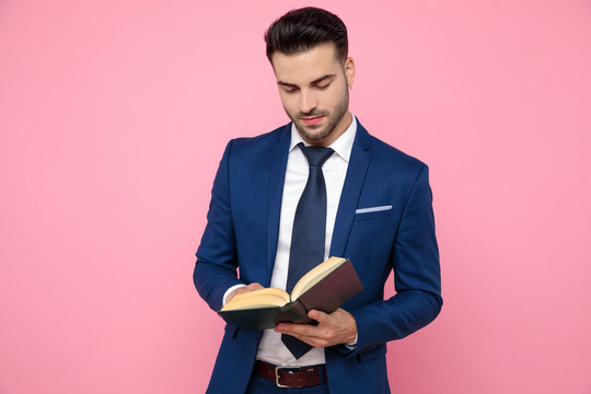 smart casual man reading on pink background in studio