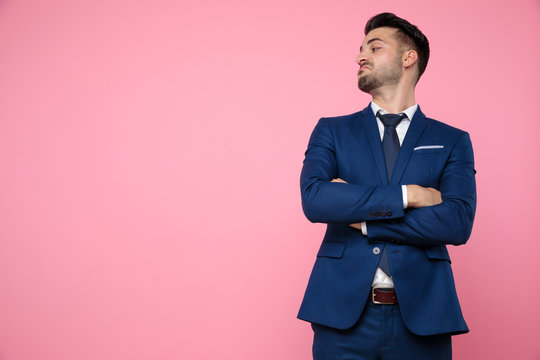 handsome young man crossing arms on pink background