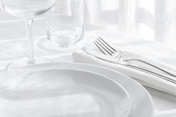 In de dag Restaurant Table setting white and grey colour. Empty glasses and plates set with napkin and cutlery on white table cloth. Restaurant interior background.