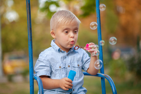 A child with Down cider plays in nature. Toddler blowing soap bubbles. Genetic abnormality in a boy.