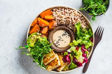 Printed kitchen splashbacks Buddha Buddha bowl with tofu, avocado, rice, seedlings, sweet potato and tahini dressing.