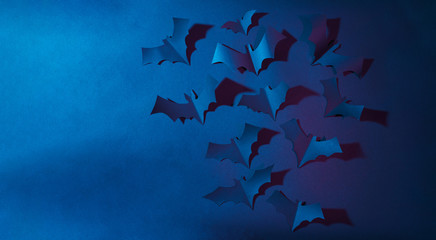 Halloween image of blue paper bats flying up on dark blue background.