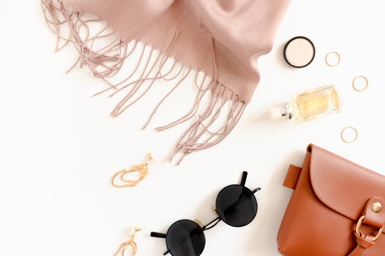 Fashion flatlay with women's cosmetics and accessories on white desk