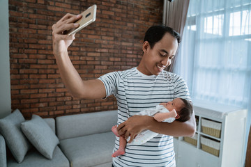 Asian father with daughter taking selfie on smartphone in the house