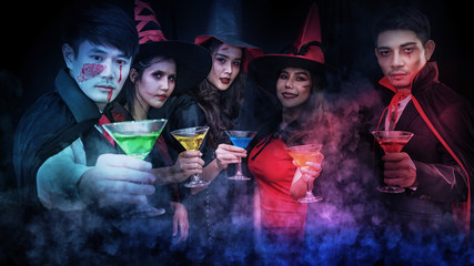 men and women Celebrating parties in evening gowns, drinking, taking pictures, dancing and pretending to be ghosts. Looking at the camera with a smile while celebrating Halloween in a nightclub.