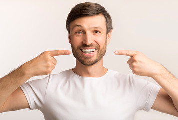 Happy Man Pointing Fingers At His Perfect Smile, White Background