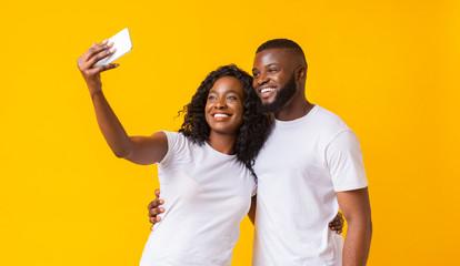 Lovely black guy and girl taking selfie on smartphone