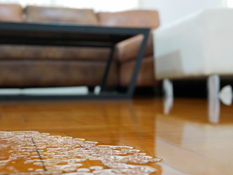 Close up of water flooding on living room parquet floor in a house - damage caused by water leakage