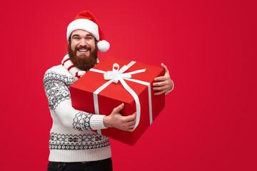 Cheerful man with huge Christmas present