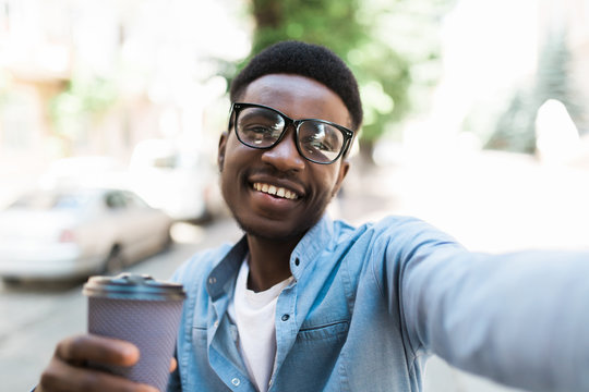 Cheerful young african guy standing outdoors holding coffee make selfie by camera.