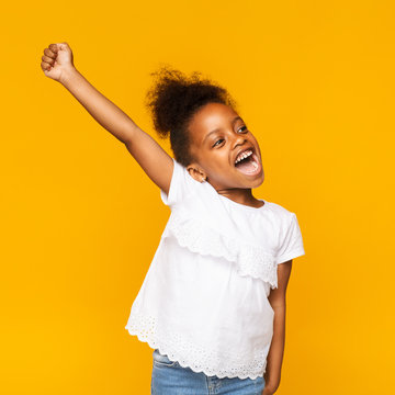 Cute african toddler girl shouting hooray on orange background