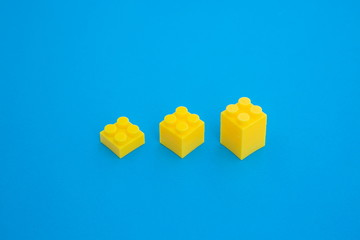 yellow cubic plastic block on blue paper background . stairs three step for growing and succeeding business isometric concept .