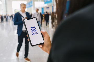 BERLIN, GERMANY AUGUST 2019:   Woman hand holding iphone Xs with logo of Libra at a conference. Libra Facebook cryptocurrency and bitcoin cryptocurrency smartphone share, Libra coins concept.