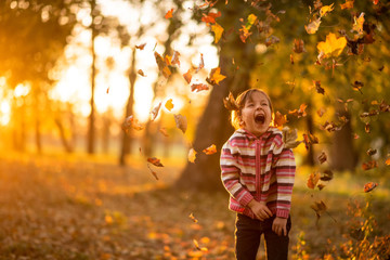 Cute little girl playing with leaves falling on her