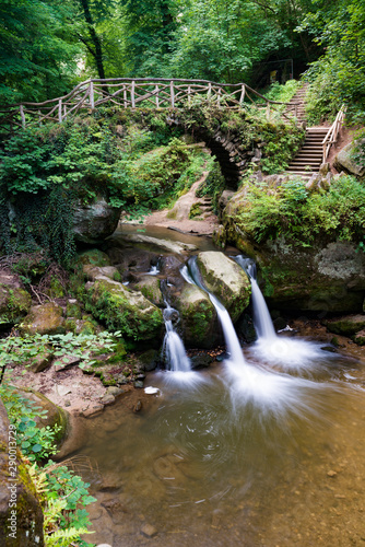 Wall mural idyllic small waterfall in lush green forest landscape with an old bridge above