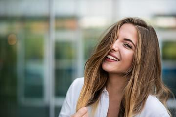 Smiling fashion model posing outdoors