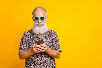 Portrait of cheerful funny funky old bearded man use his cell phone chat on summer holidays vacation wear green eyeglasses eyewear leopard shirt isolated over yellow background