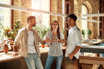 Nice coffee break. Three young and cheerful colleagues in casual wear holding coffee cups and discussing something while standing in the modern office