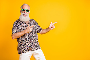 Portrait of crazy funny funky old bearded man with eyeglasses eyewear point at copyspace recommend sales discounts wear leopard print shirt isolated over yellow background Wall mural