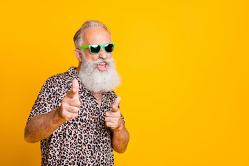 Portrait of funky old bearded man in eyeglasses eyewear feel cool crazy point at you wearing leopard shirt isolated over yellow background