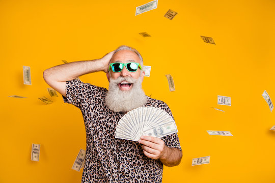 Portrait of retired old funny bearded man in eyewear eyeglasses scream omg look at falling money win lottery wearing leopard t-shirt isolated over yellow background