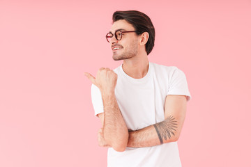 Image of young cheerful man wearing eyeglasses looking and pointing thumb aside at copyspace