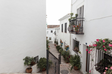 Charming narrow old streets of a white village with vintage balconies and with pink flowers in pots on the facades of houses. Small town in Spain.