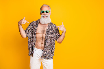 Photo of cheerful nice old man pointing at himself to show you his handsomeness while isolated with yellow background