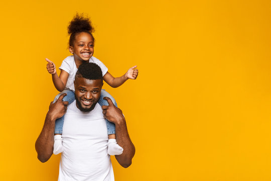 Adorable little african girl gesturing thumbs up on daddy's shoulders