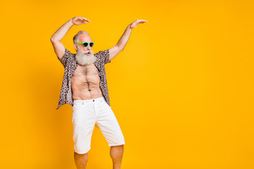 Photo of cheerful energetic old man still able to move and dance as young while isolated with yellow background