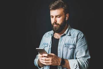 Young man using smartphone, listening music.Dark-haired bearded hipster with wireless earphones...
