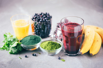 In de dag Sap Heavy metals detox smoothie. Blueberries, bilberry, barley grass juice extract, spirulina powder, orange juice, dulse and cilantro on gray background. Healthy eating, alkaline diet, vegan concept.
