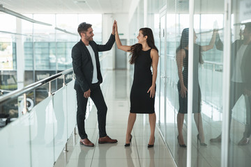 two business colleagues young beautiful woman in sexy black dress and handsome man shaking hands in the office after successful purchase deal