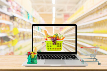 supermarket aisle blurred background with laptop computer and shopping cart on wood table grocery...