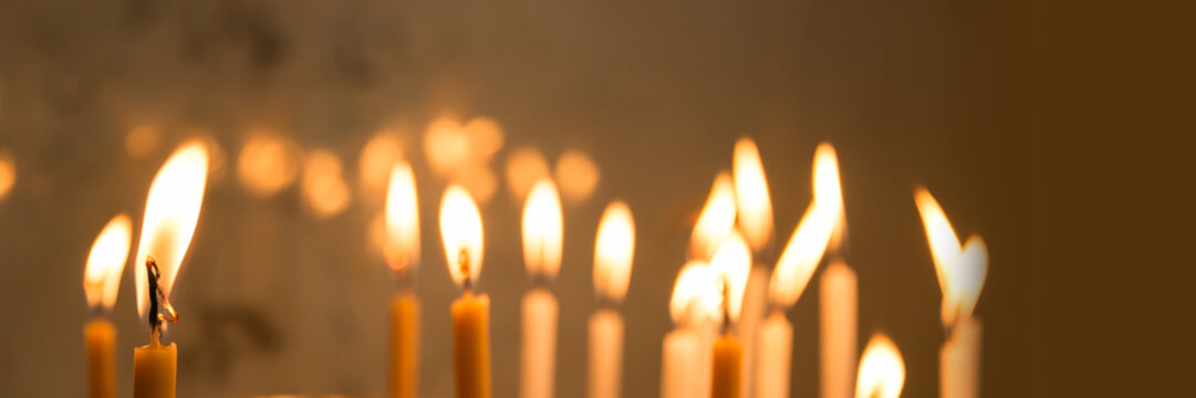 Close up of candles in a church, panoramic christmas and holiday lights background