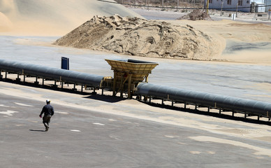 A worker walks near a pile of sand at Vaca Muerta shale oil and gas drilling, in the Patagonian province of Neuquen