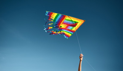 Horizontal image of a woman's hand taking a colorful flying kite against the blue sky. Freedom concept