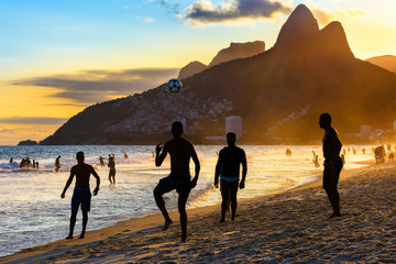 Fotomurales - Brazilian boys play football on Ipanema beach at sunset in Rio de Janeiro, Brazil.