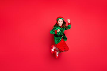 Full length body size view of nice attractive cheerful cheery funny funky overjoyed small little pre-teen elf having fun rejoicing isolated over bright vivid shine red background