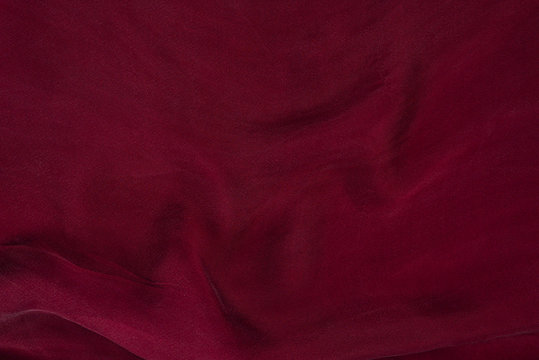 Soft smooth burgundy silk fabric background. Fabric texture.