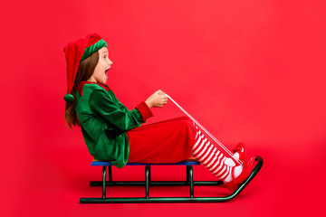 Full length profile side photo of excited elf kid in hat with long red head haircut sledding screaming wearing cap costume isolated over red background