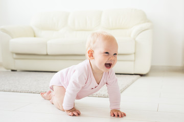 Smiling crawling baby girl at home on floor