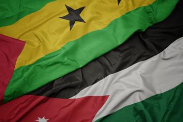 waving colorful flag of jordan and national flag of sao tome and principe .