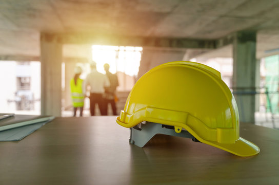yellow safety helmet on workplace desk with construction worker team engineer or inspector checking new project contract at construction site background, engineering, construction, contractor concept