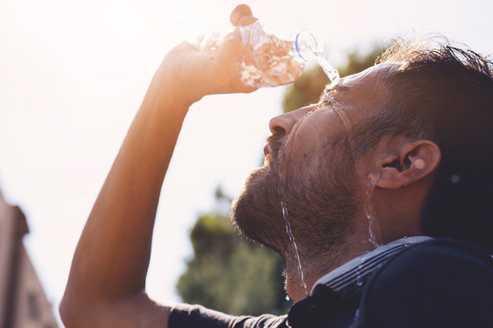 Young man splashing and pouring fresh water from a bottle on his head to refresh against a blue sky background in a summer heat