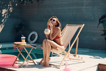 Attractive young woman in bikini relaxing and enjoying refreshing cocktail while sunbathing on the poolside outdoors