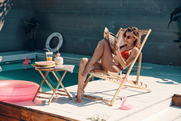 Attractive young woman in bikini reading magazine while sunbathing on the poolside outdoors