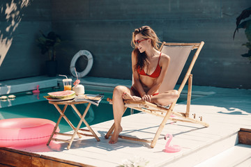 Attractive young woman in bikini relaxing and smiling while sunbathing on the poolside outdoors