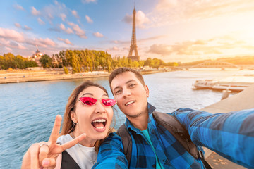 A happy couple in love a man and a woman embrace and take a selfie on the banks of the Seine river with the Eiffel tower in the background. Travel and vacation in Paris and France