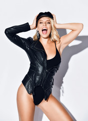 Happy screaming blonde woman in black bodysuit and stylish leather jacket is holding her head yelling